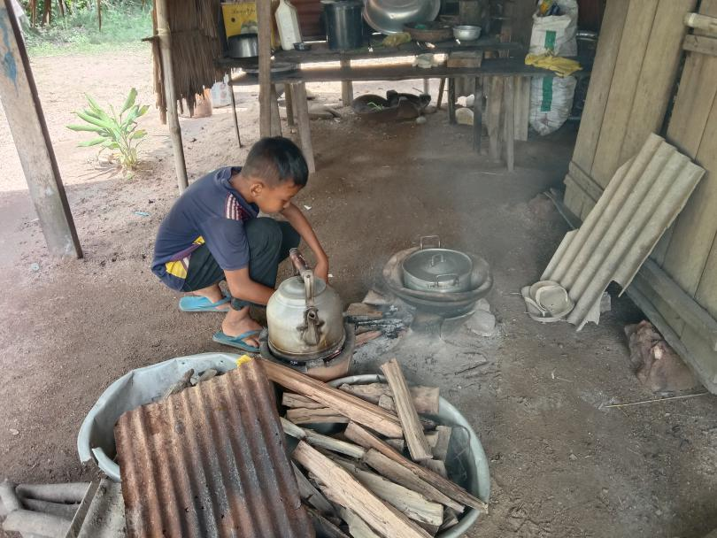 Sochen cooking rice at his home
