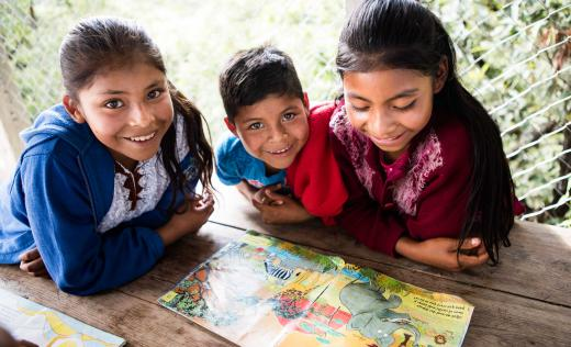 Two girls and a boy reading a book at school in Guatemala