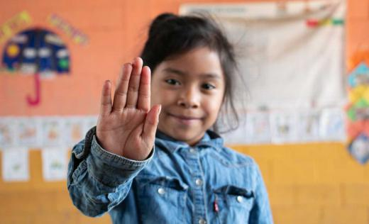 Little girl at school environment from Guatemala, with a hand up