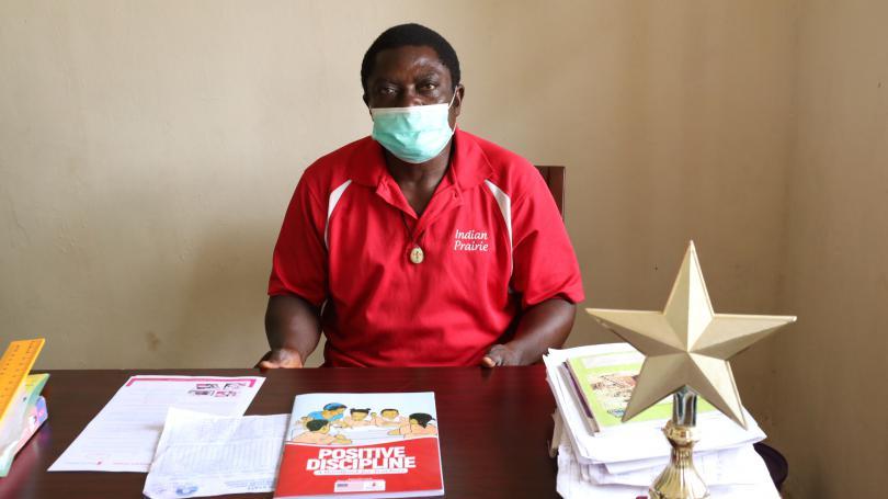 A head teacher (Mr Boniface) sitting behind his office desk