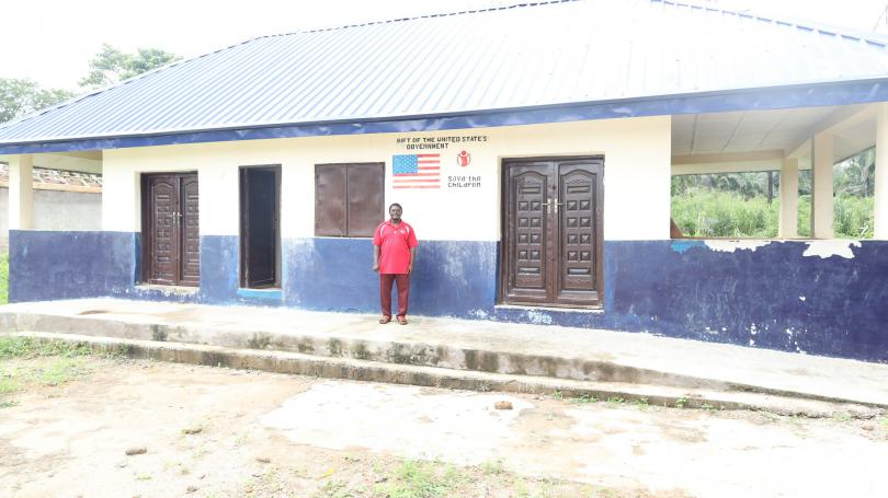 Mr Boniface standing in front of the block built by SCI in his school