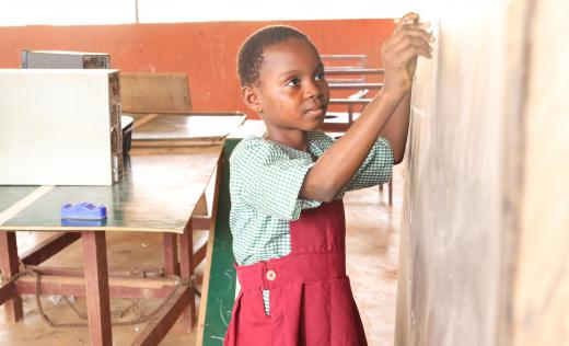 A girl child writing on a black board in a classroom