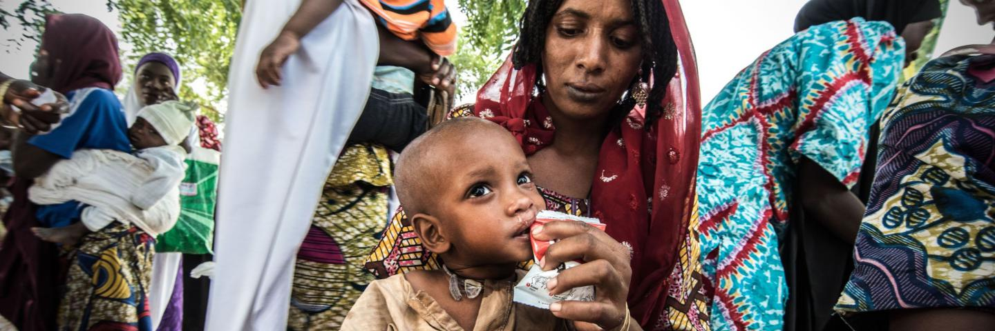A mother feeds protein rich therapeutic food to her child at the Dusuman health clinic Outpatient Therapeutic Unit near Maiduguri