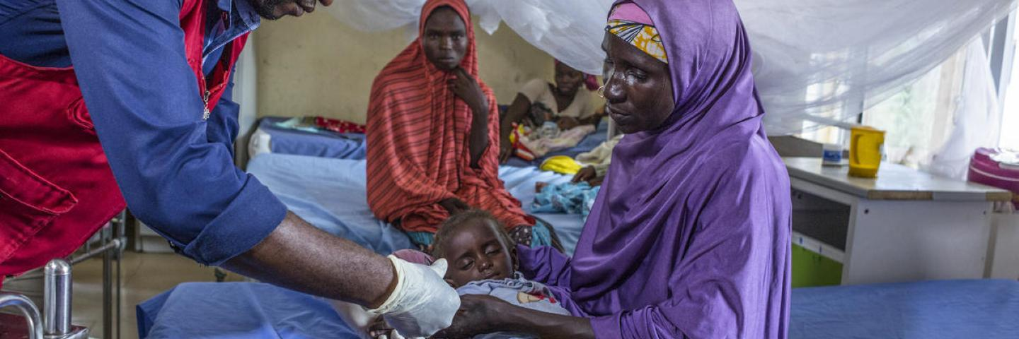 A nurse administers intravenous drugs to a patient with severe acute malnutrition.