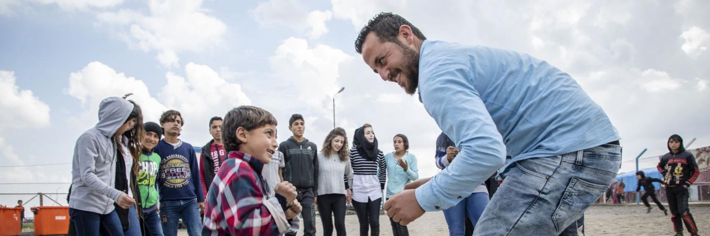 Sami*, eight, dances dabke, a traditional dance from the region, with an activities facilitator at Save the Children's Child Friendly Space in a displacement camp, North East Syria.
