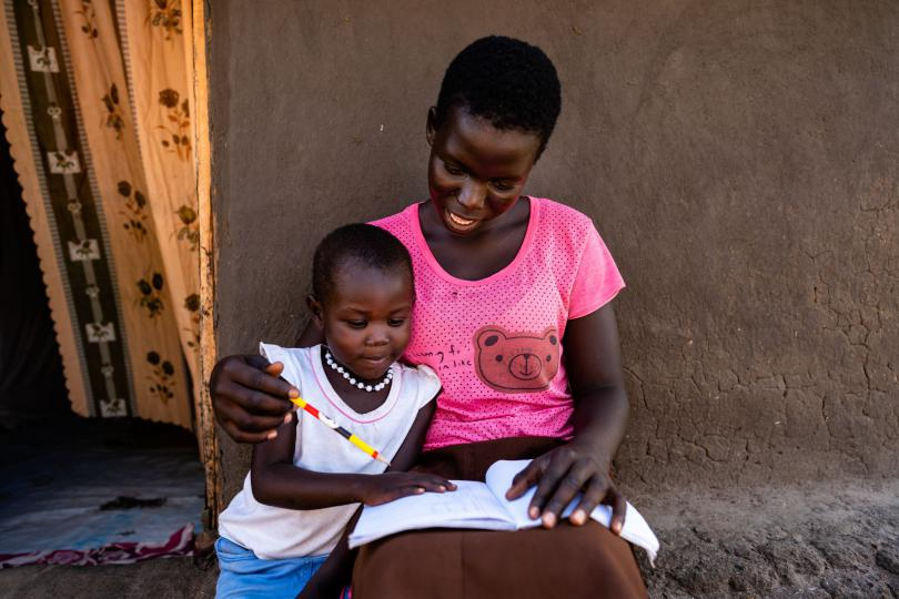 Harriet showing her young sister her homework. Louis Leeson / Save the Children