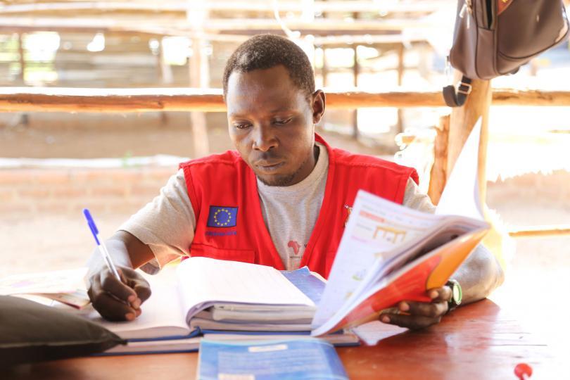 Teacher David Elias marking books. Alun McDonald / Save the Children