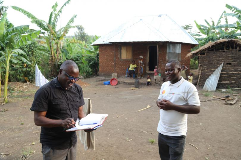 John (right) outside his new family home, with Save the Children staff member John Mateso (left)