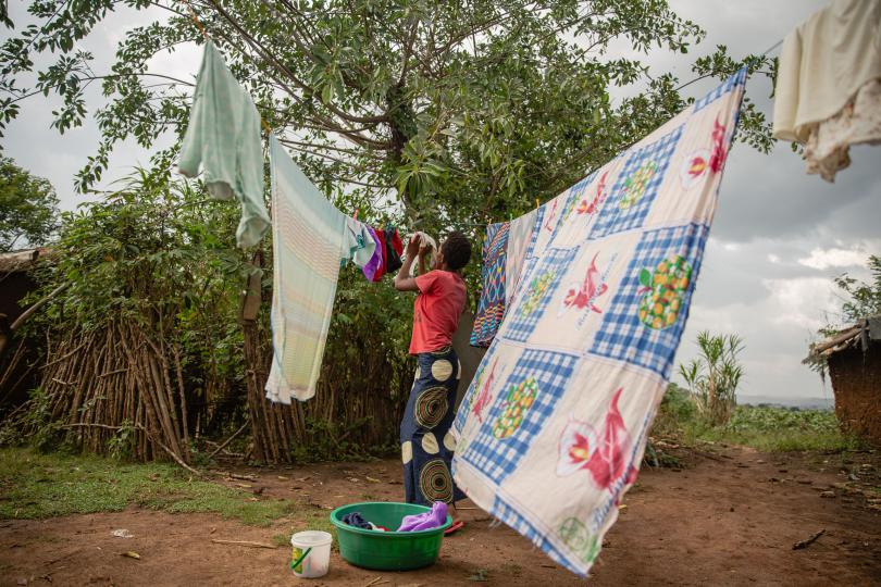 Lydia hangs up her baby's clothes. Esther Mbabazi / Save the Children