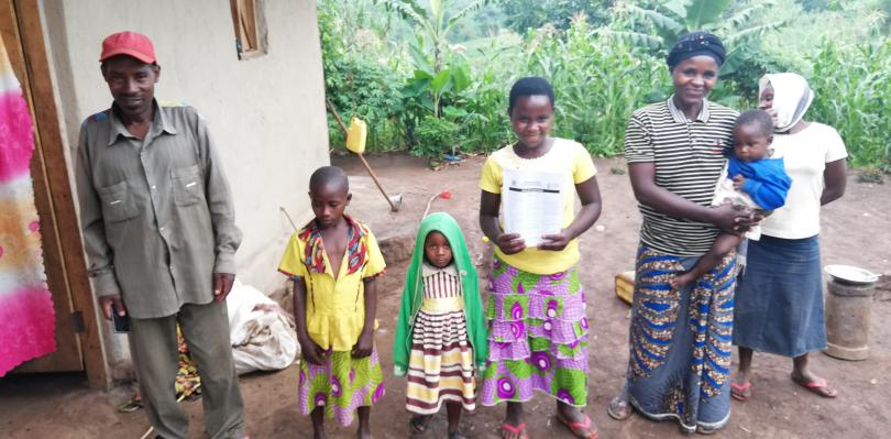 Priscille*, holding learning materials with her family
