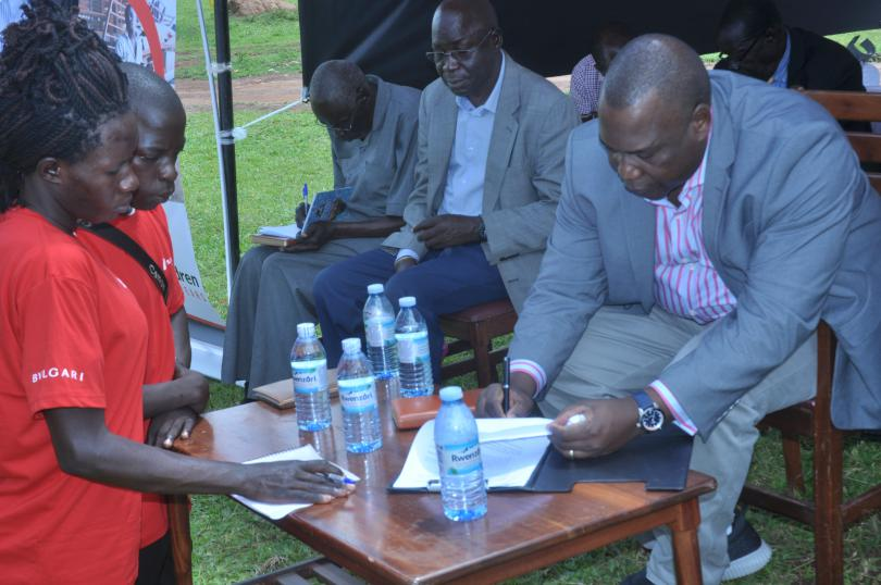 HRH David Onen Acan II signs the youth advocates' petition. Immaculate Nalubyayi / Save the Children