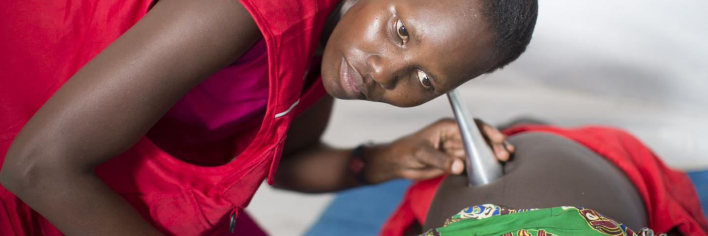 Midwife attending to pregnant woman.