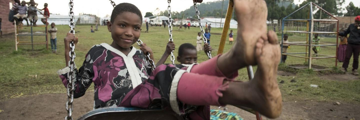 Child playing on swing at a refugee settlement in western Uganda
