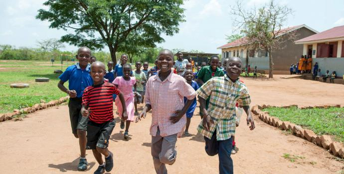 Children run to school in central Uganda. Andrew Pacutho / Save the Children