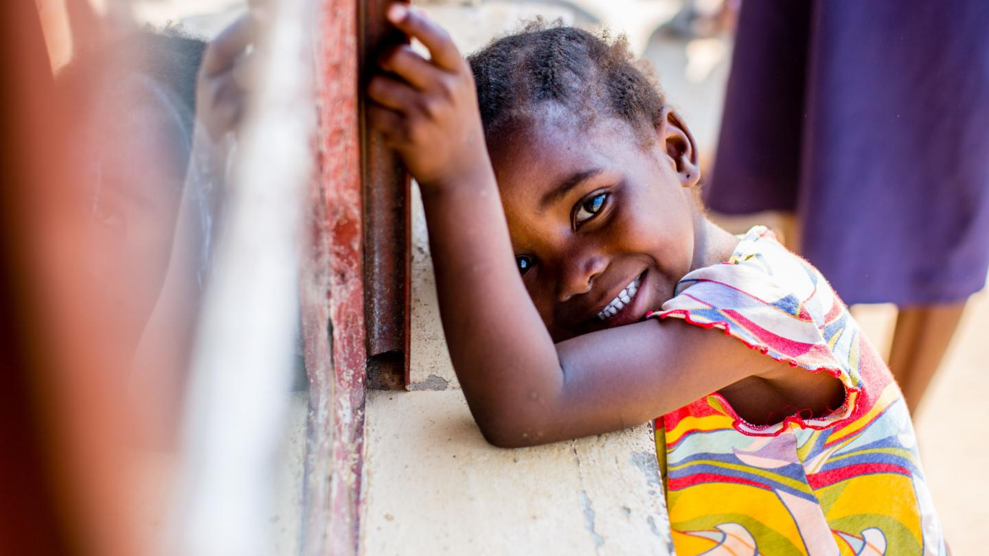 A young girl waits outside of her school