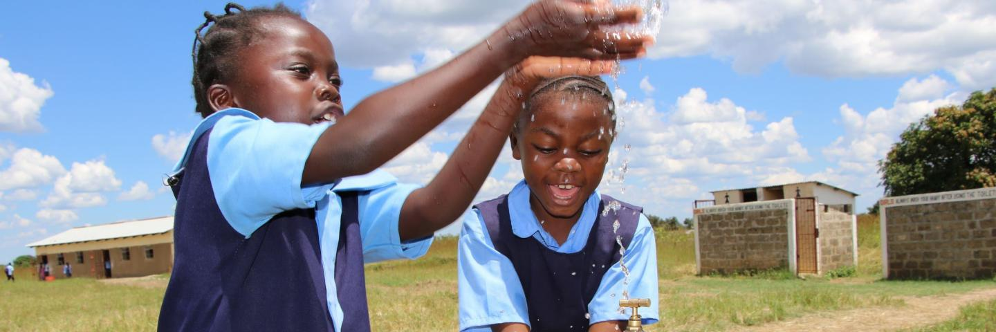 Girls play with water tap