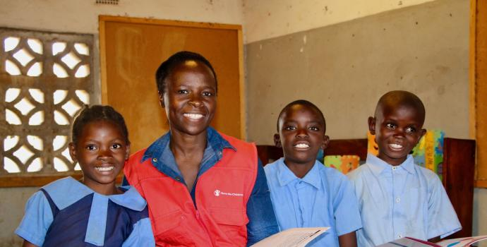 SCI Staff reading books with Masuwa and her classmates - Zambia